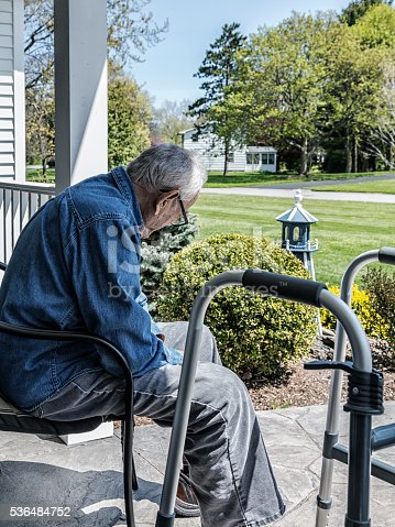 On a sunny day, an elderly senior adult 93 year old man with a physical impairment is sitting partly in shadows near his orthopedic walker on his home front porch.