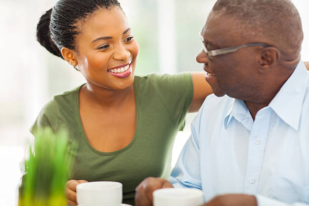 elderly african american man enjoying coffee with his granddaughter stock photo