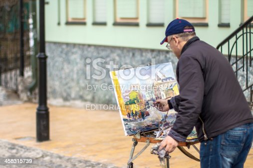 istock Elderly artist paints a picture of oil 458315739