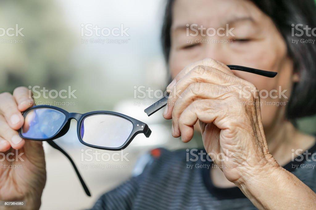 Elderly asian woman repair broken glasses stock photo