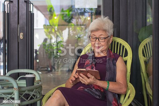 Senior woman using a mobile phone while sitting on bench in her backyard garden