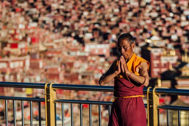 Un monje budista ancianos orando fuera de un templo. - foto de stock