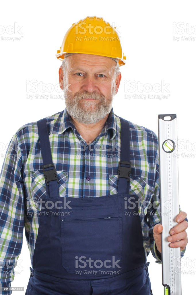 Elderly builder with spirit level tool stock photo
