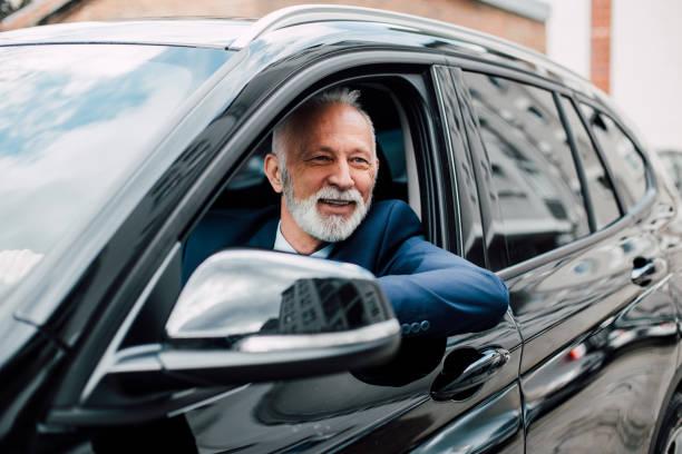 elderly business man in a car - old men window imagens e fotografias de stock