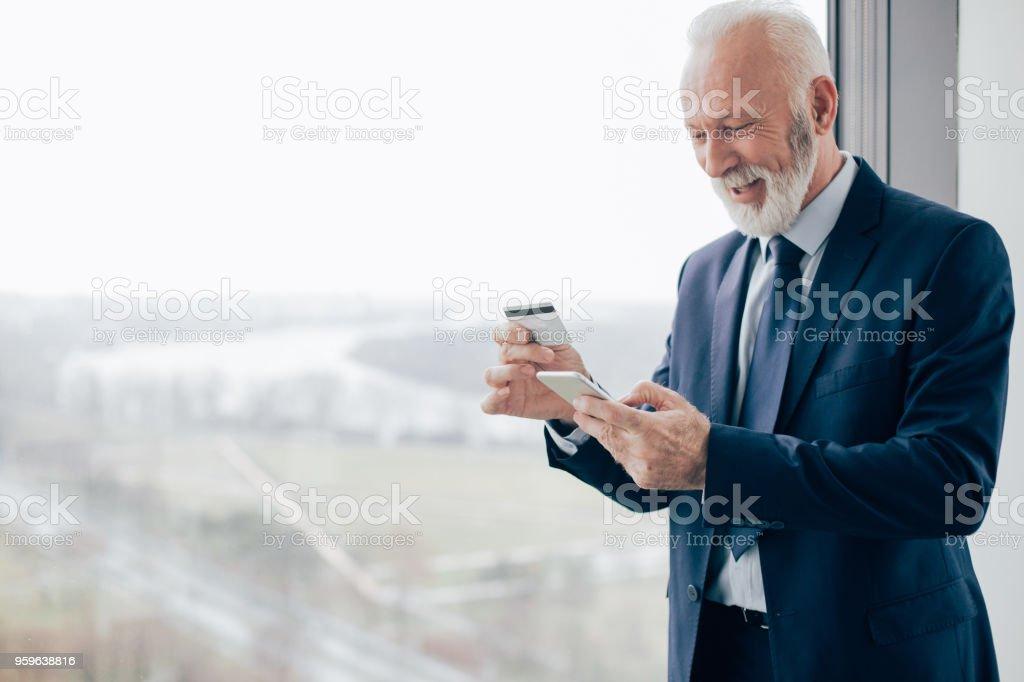 Hombre de negocios mayores tecleando en el teléfono y mantener la tarjeta de crédito - Foto de stock de Adulto libre de derechos