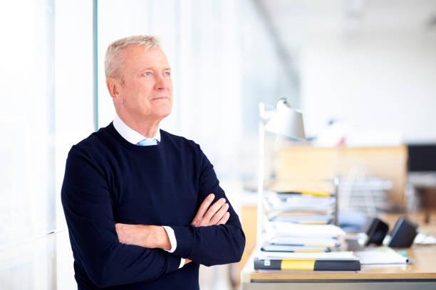 Ältere Geschäftsmann-Porträt, während stehen mit den Armen im Büro gekreuzt – Foto