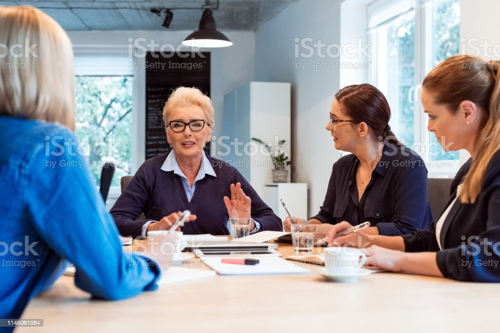 Elderly businesswoman planning with colleagues Elderly professional discussing plan with female colleagues. Expertise are working together in new business. They are sitting in office. 35-39 Years Stock Photo