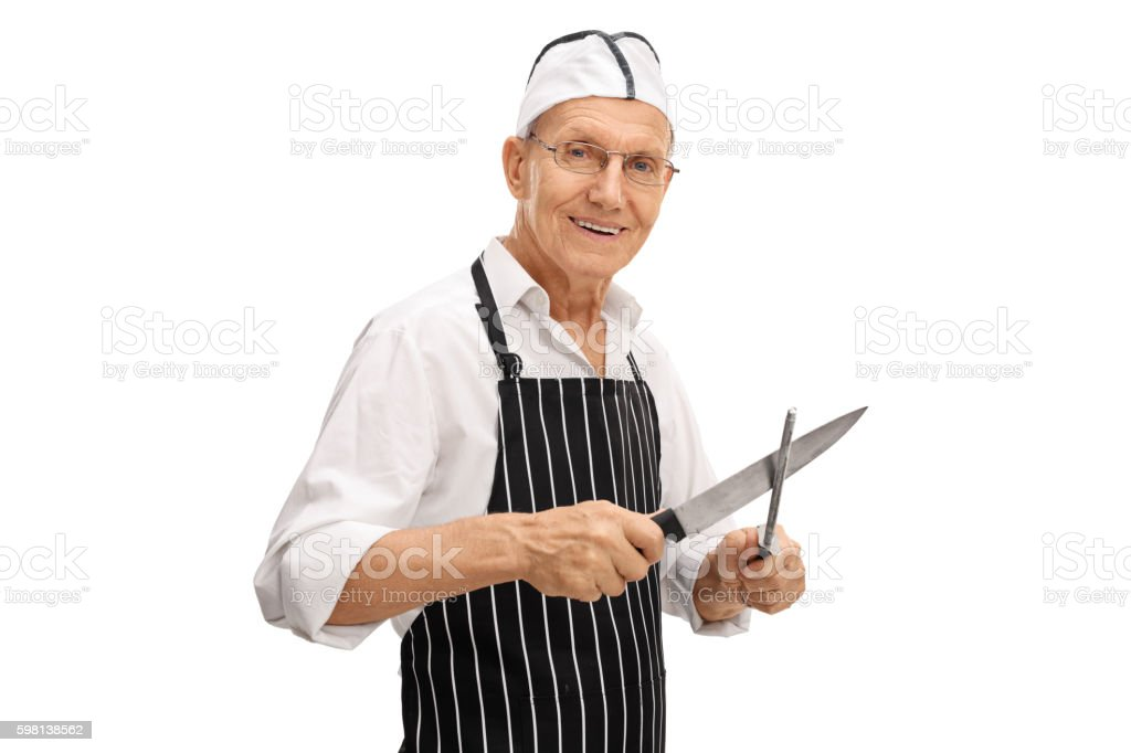 Elderly butcher sharpening his knife stock photo
