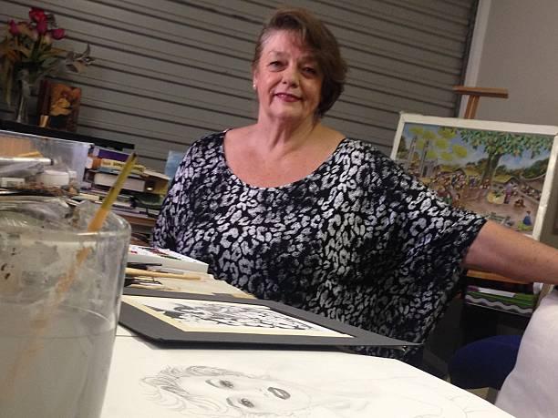 Elderly Care female sits at desk stock photo