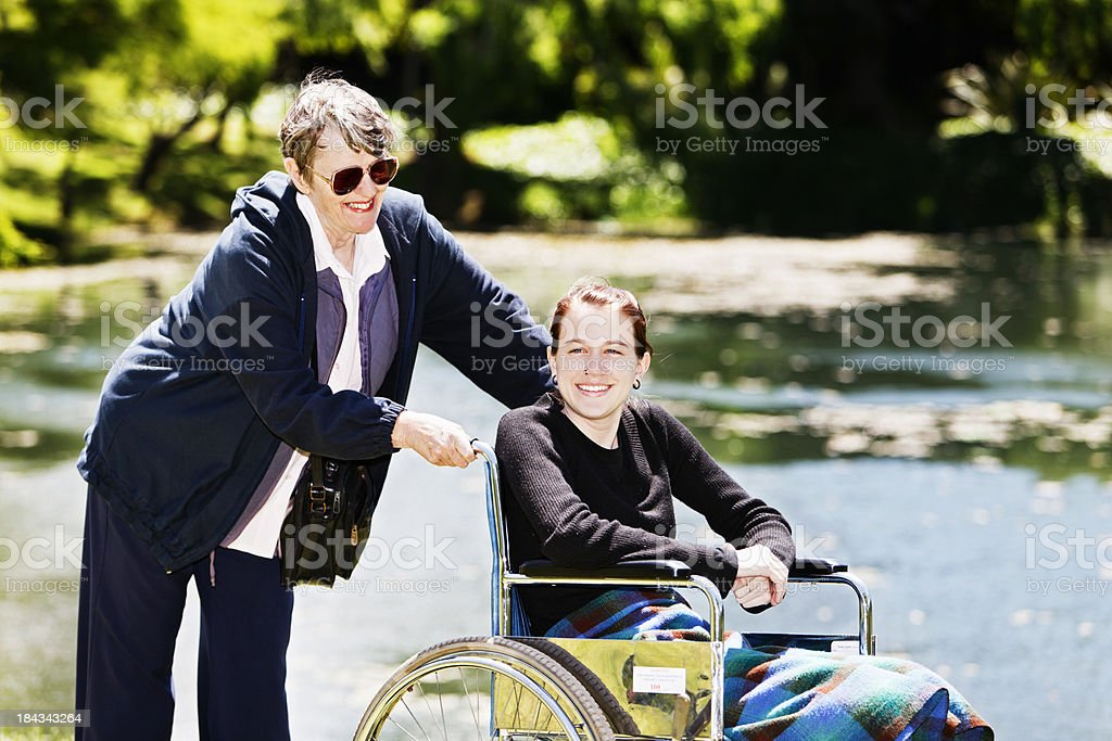 Elderly caregiver smiles affectionately at happy teenager in wheelchair stock photo