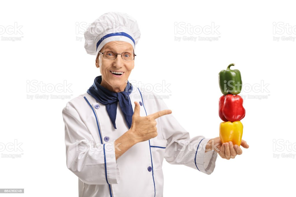 Elderly chef with peppers pointing royalty-free stock photo
