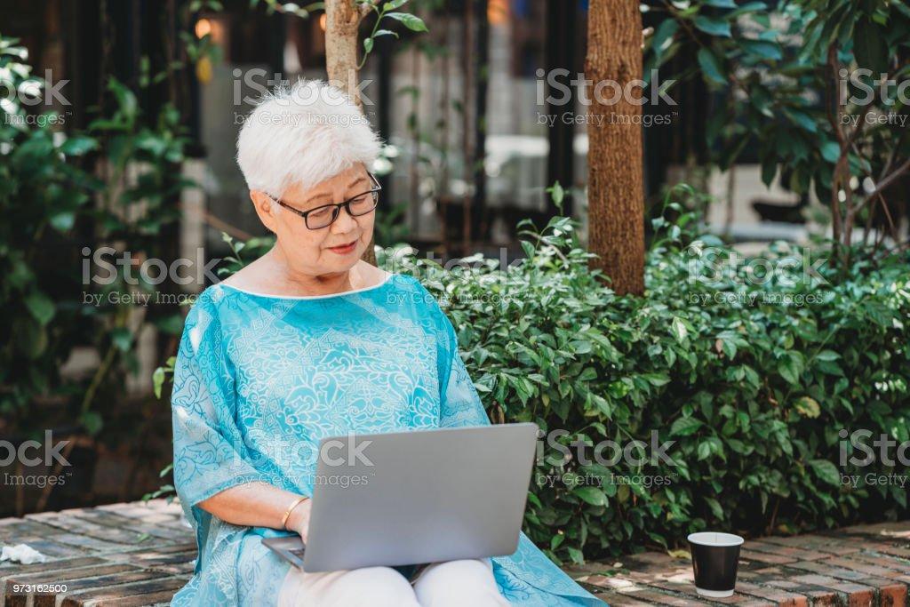 Ältere Chinesin, die im Internet Surfen mit Laptop im Garten zu sitzen – Foto