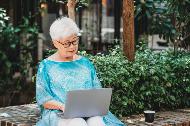 Elderly chinese woman surfing the net with laptop sitting in the garden stock photo