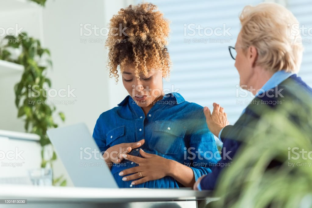 Elderly colleague talking to pregnant professional Elderly colleague talking to pregnant businesswoman sitting with hands on stomach. Business professionals are discussing in office. They are communicating at workplace. 35-39 Years Stock Photo