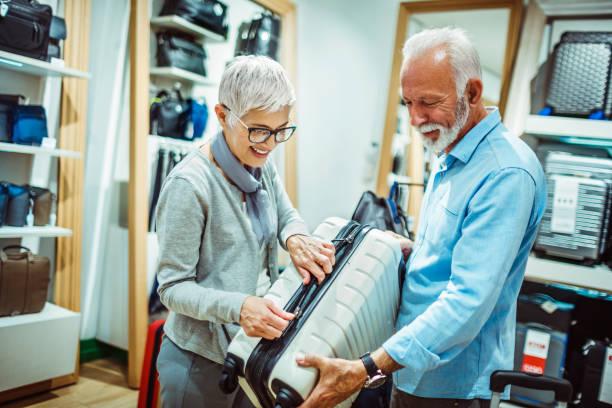 älteres ehepaar wählen einen weißen reise koffer im ladengeschäft taschen und portemonnaies - trolley kaufen stock-fotos und bilder