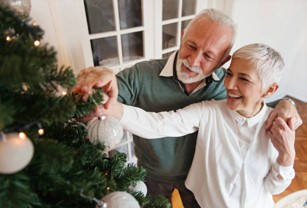 Elderly couple decorating a Christmas tree stock photo