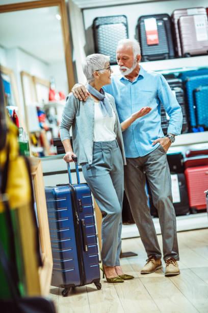 älteres ehepaar, die diskussion über den kauf eines blauen reisen, koffer, taschen und accessoires vorrätig - trolley kaufen stock-fotos und bilder