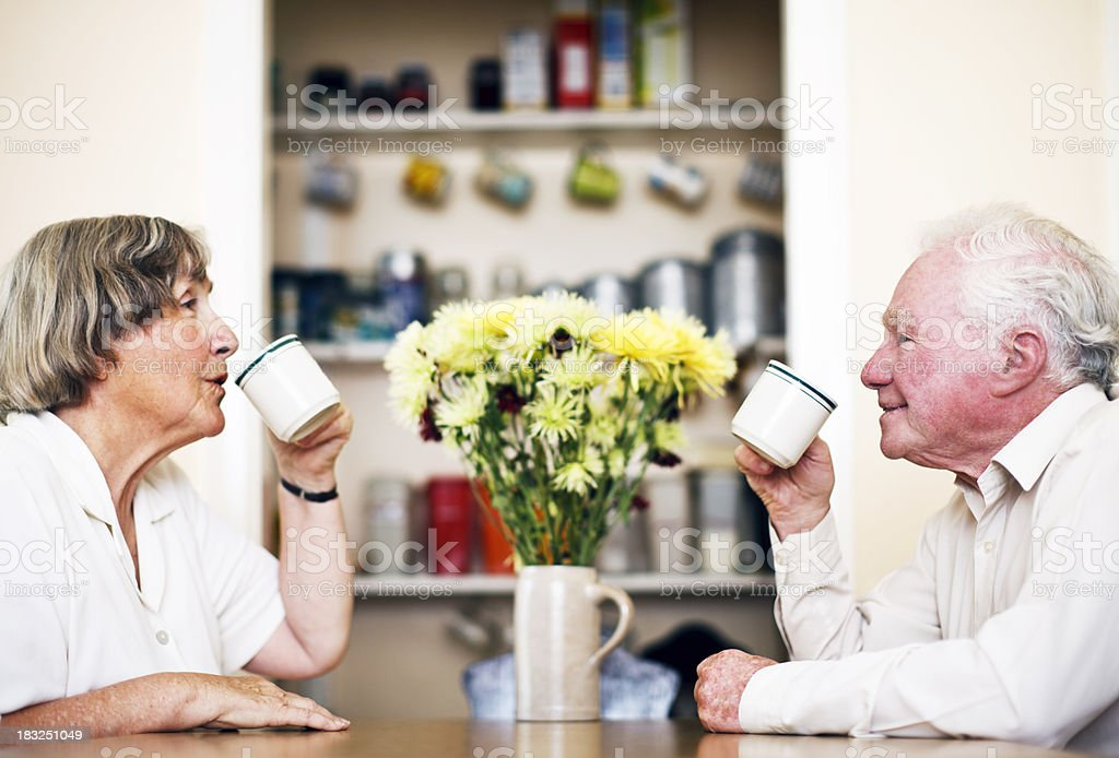 Elderly couple drink coffee together at home royalty-free stock photo