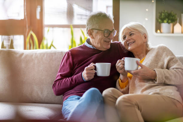 Elderly couple drinking coffee together on the sofa at home stock photo