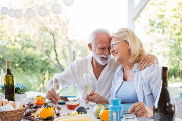 pareja de ancianos bebiendo vino disfrutando de su cena - couple lunch outdoors fotografías e imágenes de stock