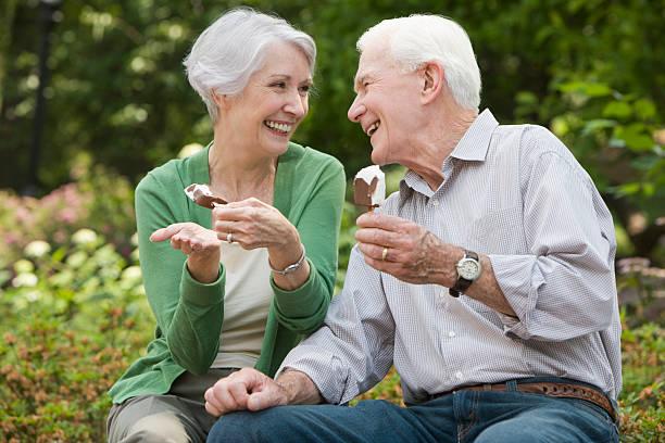 Elderly couple eating ice cream and smiling stock photo