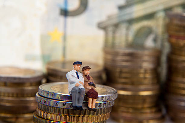 Elderly couple figurine placed on stacks of coins stock photo