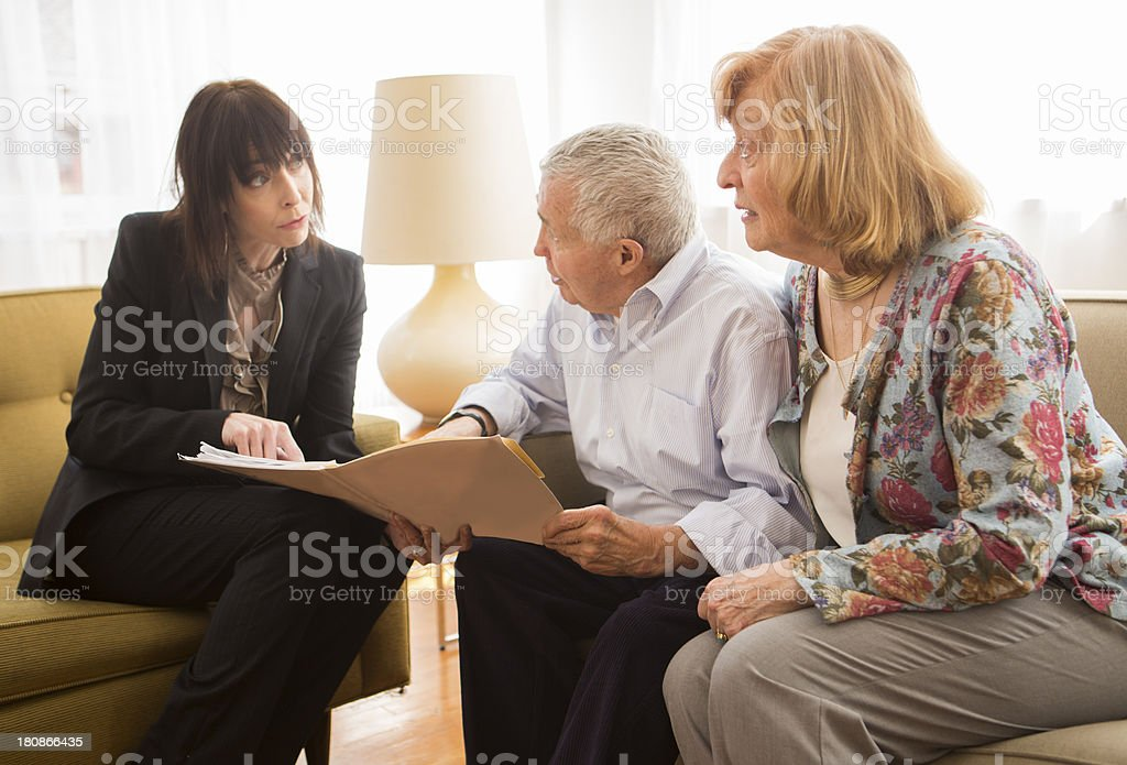 An elderly couple getting information from a salesperson or agent.