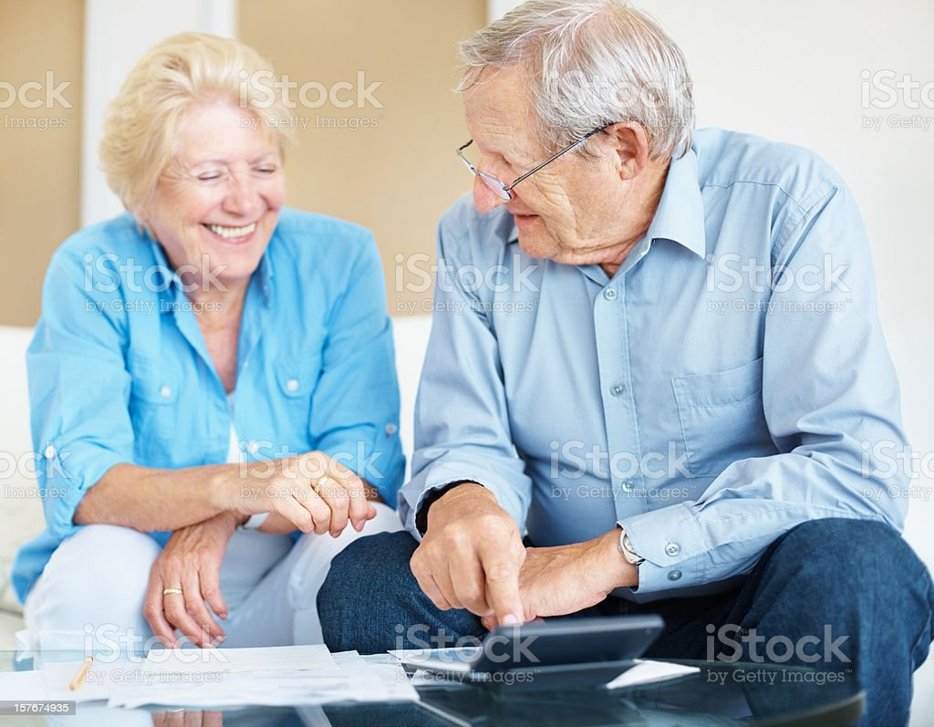 Elderly couple happy over the results after calculating their expenses royalty-free stock photo