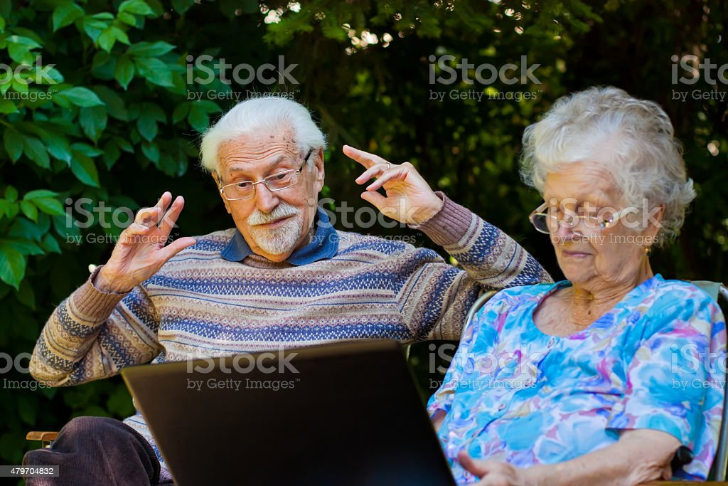 Elderly couple having fun with the laptop outdoors stock photo