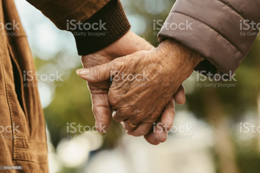 Elderly couple holding hands and walking stock photo