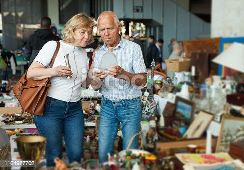 istock Elderly couple in flea market chooses antique items 1164977702
