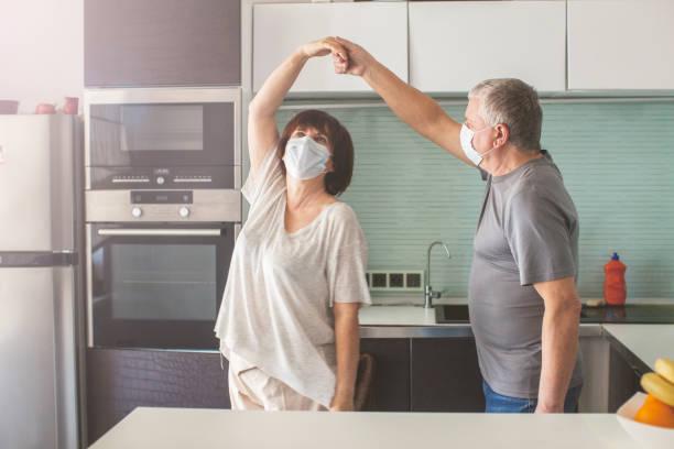 Älteres Paar in medizinischen Masken während der Pandemie Coronavirus tanzen – Foto
