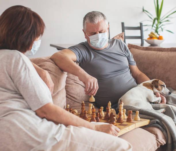 Elderly couple in medical masks during the pandemic coronavirus play chess stock photo