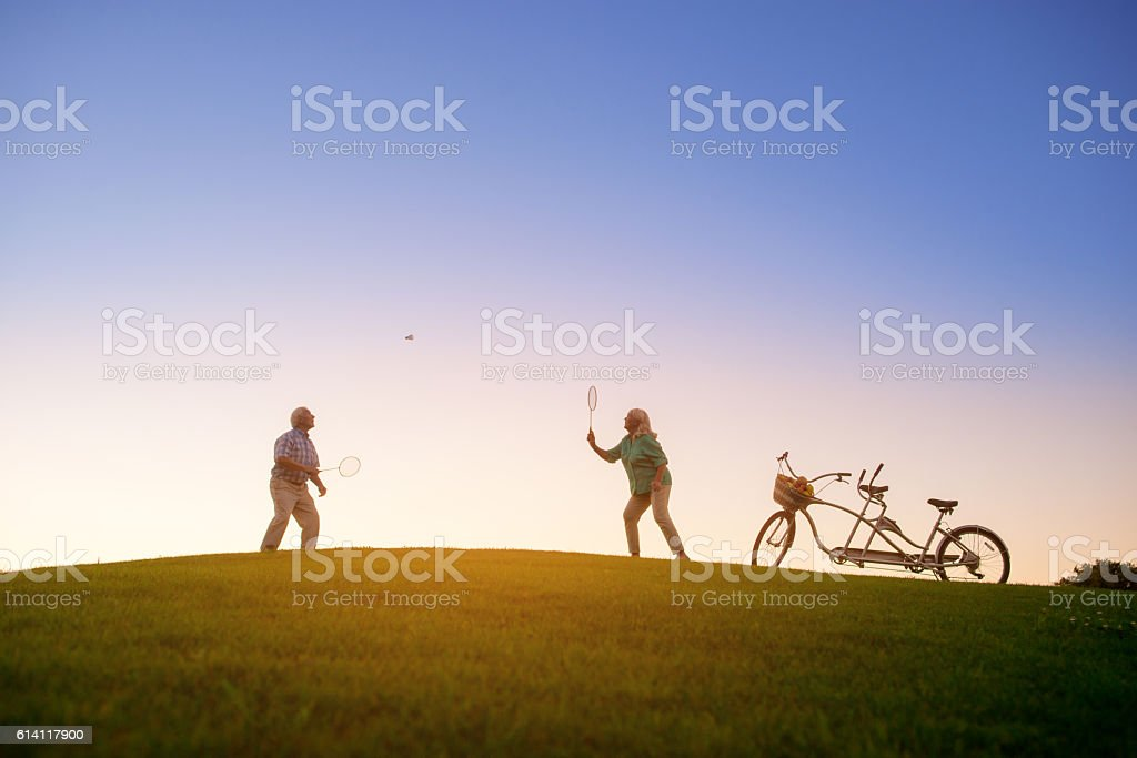 Elderly couple is playing badminton. stock photo
