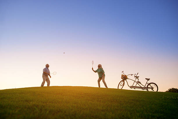 elderly couple is playing badminton. - bádminton deporte fotografías e imágenes de stock