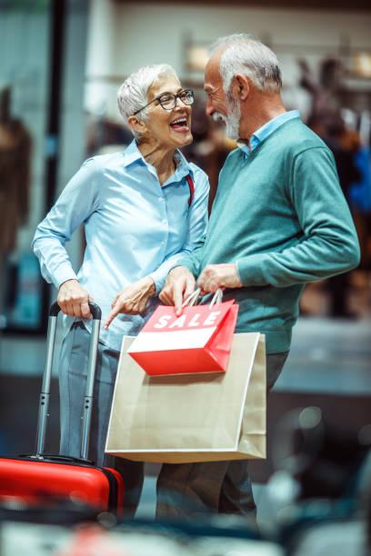 älteres ehepaar mit freude auf die dinge zeigen kauften sie nach einem einkaufsbummel in einer shopping mall - trolley kaufen stock-fotos und bilder