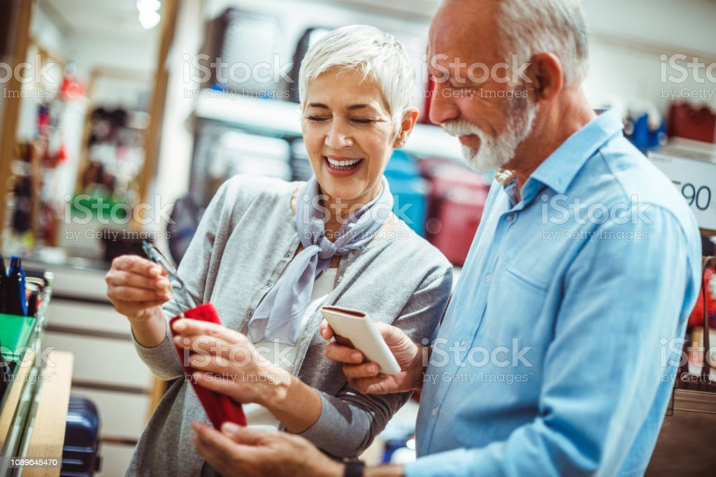 Senior couple looking at a pair of eyeglasses and a wallet in a bags...