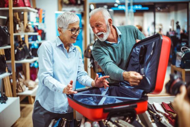 älteres ehepaar blick auf einem roten koffer im ladengeschäft taschen und portemonnaies - trolley kaufen stock-fotos und bilder
