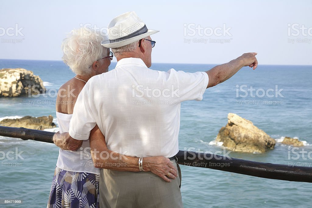 Elderly couple looking out across the ocean royalty-free stock photo