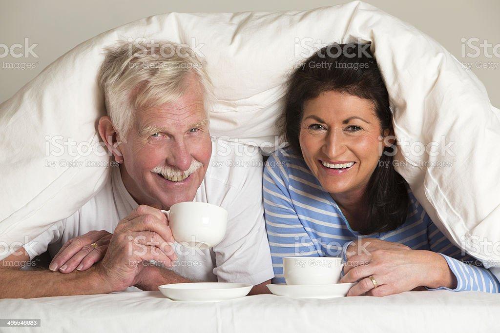 Русская пожилая пара лежат в кровати