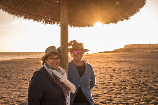 Elderly couple of woman with sun backlight at the beach
