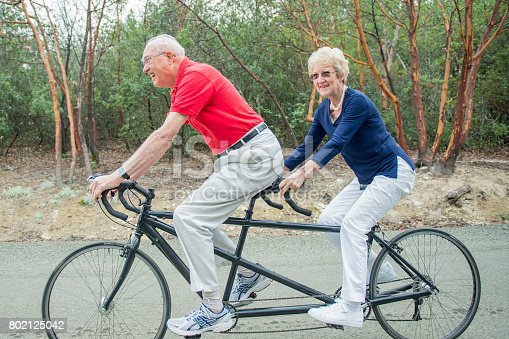 An elderly Caucasian couple are riding a tandem bicycle together. They are traveling down a road among some trees.