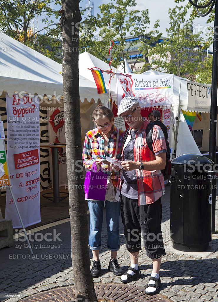Elderly couple ouside the church stall at Pride festival royalty-free stock photo