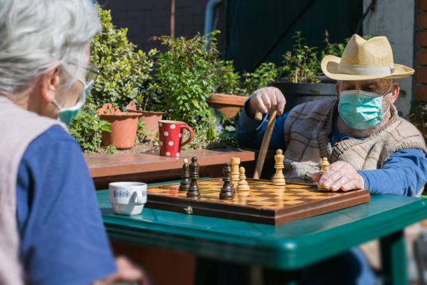 pareja de ancianos jugando ajedrez en la terraza durante la cuarentena epidémica coronavirus - foto de stock