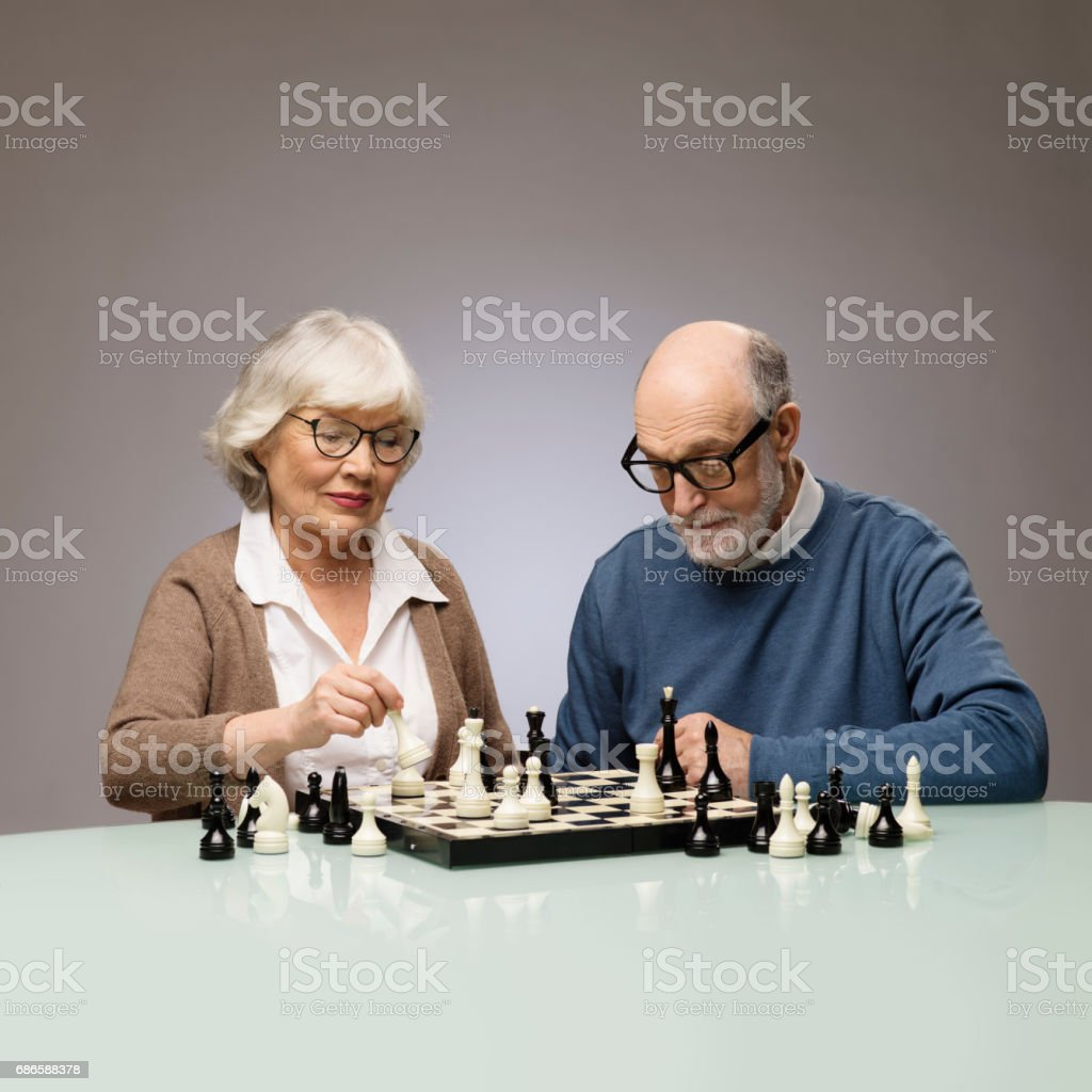 Elderly couple playing chess royalty-free stock photo