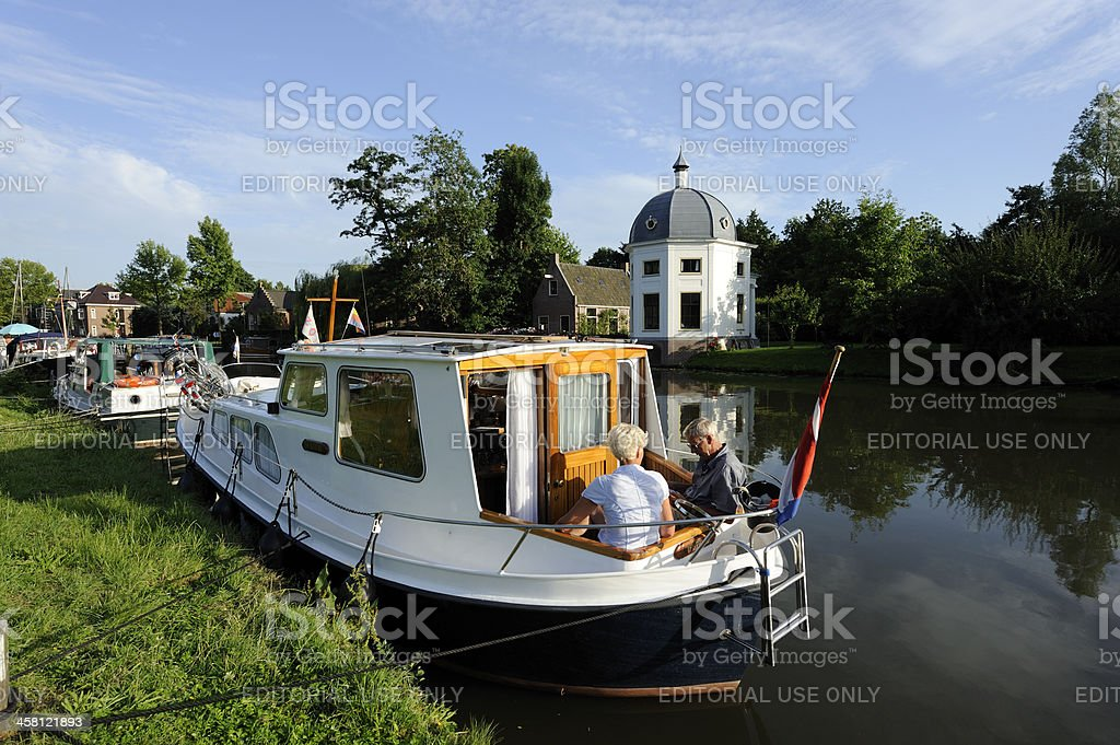 Elderly couple relaxing on their privately-owned recreational boat royalty-free stock photo
