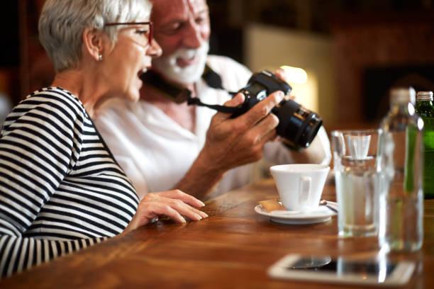 älteres ehepaar überprüfen einige fotos auf einer kamera zusammen sitzen in einem café - senior bilder wasser stock-fotos und bilder