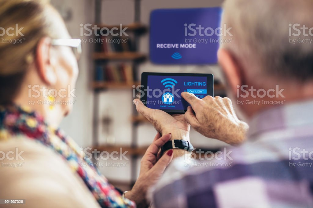 Elderly couple sitting comfortably on a sofa with their backs holding remote home control system on a digital tablet stock photo