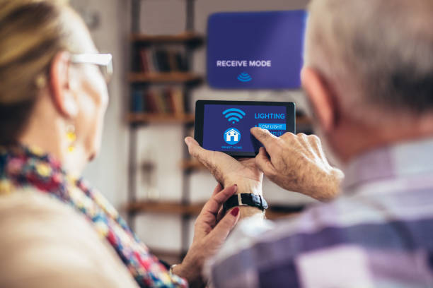 elderly couple sitting comfortably on a sofa with their backs holding remote home control system on a digital tablet - home automation stock pictures, royalty-free photos & images