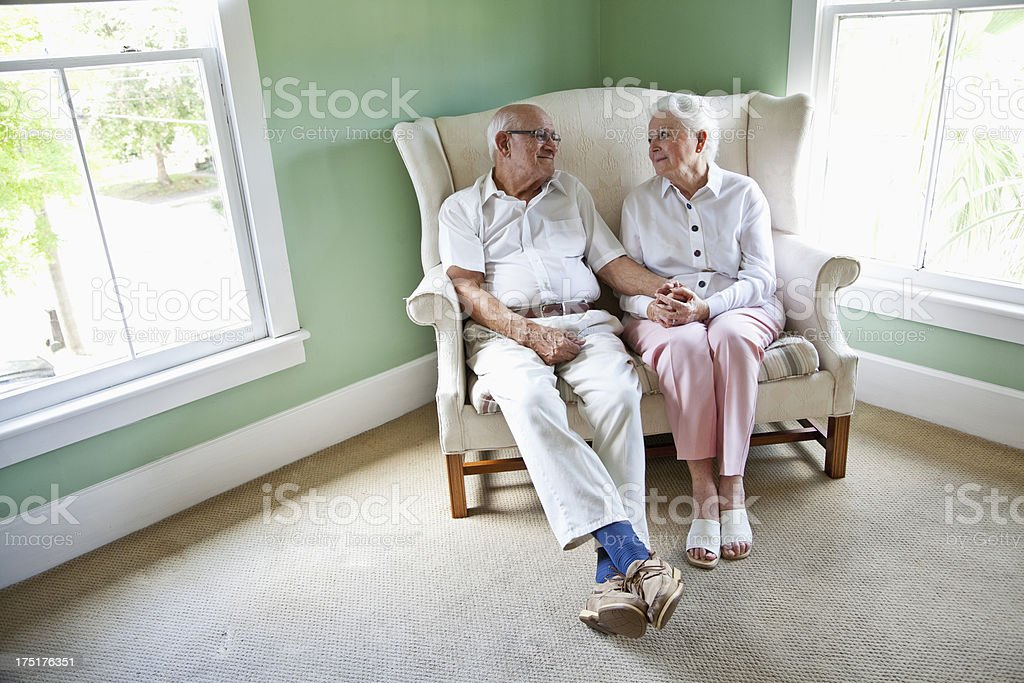 Elderly couple sitting together on love seat royalty-free stock photo